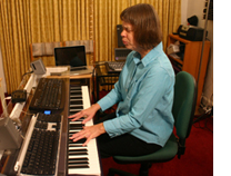 Picture: Veronica singing and playing a synthesizer keyboard. She is surrounded by studio equipment.