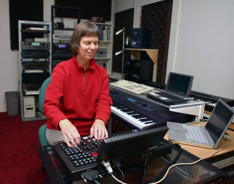 Picture: Veronica in her studio! She is sitting with her hands on the controls of the Radar hard disk recorder; appears to be listening, with a half-smile; surrounded by computer and synthesizer keyboards. In the background you see speakers and other gear.