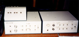 Here is a picture of two audible VU  meters with a small switch box sitting on top of one of them. Each  meter is a large rectangular box with nine switches and three knobs. Caption: