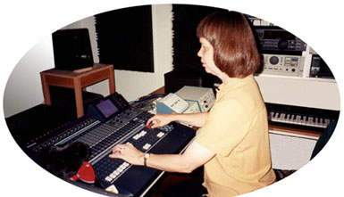 Here is a picture of Veronica at the mixing console. It shows her listening intently to the speakers and adjusting faders. It also shows the audible VU meters, a teddy bear, and some of her recording  equipment.